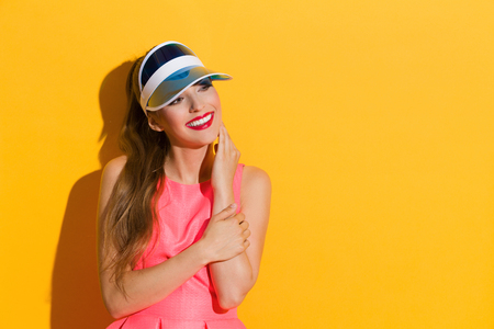 waist shot: Smiling young woman in pink dress and sun visor posing against yellow background and looking away. Waist up studio shot.