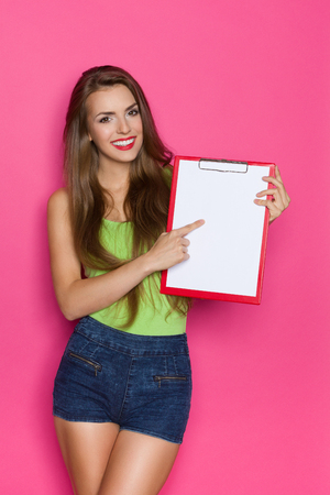 three quarter length: Smiling young woman holding clipboard and pointing. Three quarter length studio shot on pink background.