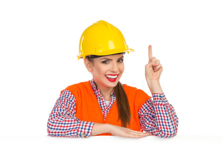 lumberjack shirt: Smiling beautiful young woman in yellow hardhat, orange reflective vest and lumberjack shirt posing behind big white banner and and pointing up. Studio shot isolated on white.