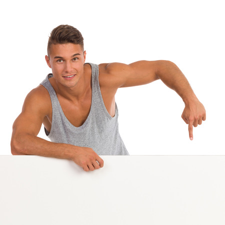 waist shot: Cheerful young man in gray shirt leaning on a white banner and pointing. Waist up studio shot isolated on white.