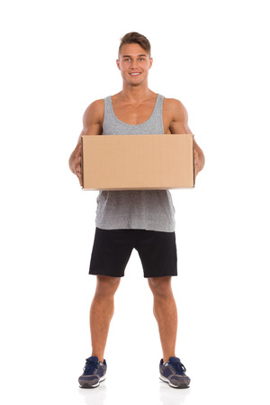legs apart: Smiling young man in black shorts and sneakers standing with legs apart and holding carton box. Full length studio shot isolated on white.