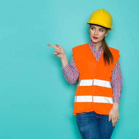 three quarter length: Cheerful young woman in orange reflective vest, yellow hardhat and jeans looking at teal copy space and pointing. Three quarter length studio shot on turquoise background.