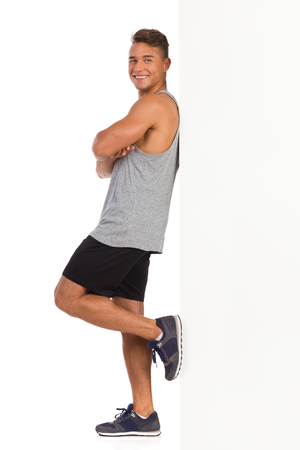 Smiling young man in sport clothes standing and leaning on a whit wall. Side view. Full length studio shot isolated on white. Stock Photo