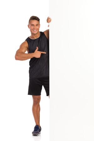 hombre deportista: Hombre joven sonriente en camisa y pantalones cortos de deporte negro de pie detrás de la bandera grande y apuntando. Estudio de longitud completa aislado disparo en blanco. Foto de archivo