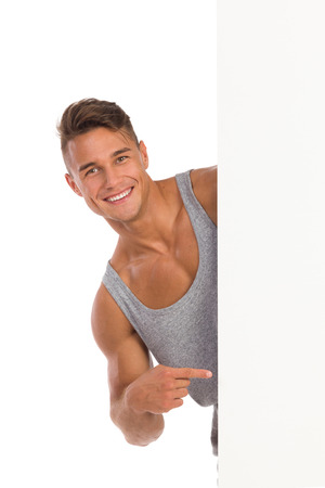 waist shot: Smiling young man in gray shirt peeking behind banner and pointing. Waist up studio shot isolated on white. Stock Photo