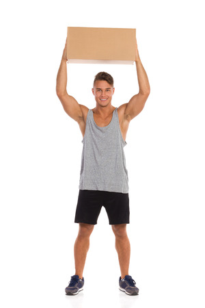 legs apart: Smiling young man in black shorts and sneakers standing with legs apart and holding carton box over his head. Full length studio shot isolated on white. Stock Photo