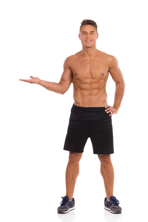 legs apart: Smiling muscular man in black shorts standing with hand raised and presenting product. Full length studio shot isolated on white.