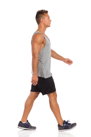 legs apart: Young man in beige shorts, blue shirt and sneakers walking. Side view. Full length studio shot isolated on white.
