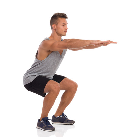 Muscular man showing a squat exercise, side view. Full length studio shot isolated on white.