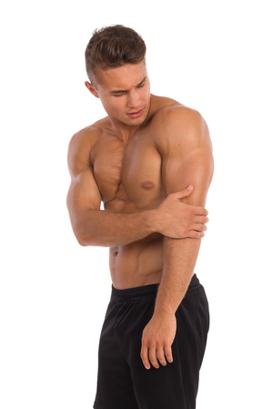 three quarter length: Young muscular man in holding elbow in pain. Three quarter length studio shot isolated on white.