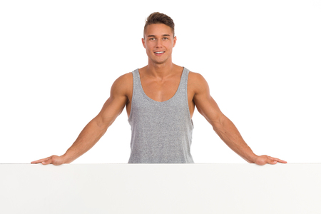 open shirt: Smiling young fit man in gray shirt standing behind big placard. Waist up studio shot isolated on white. Stock Photo