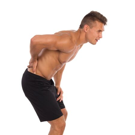 stretching condition: Young muscular man in holding lower back in pain. Full length studio shot isolated on white.