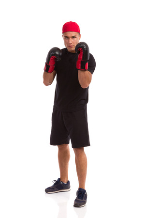legs apart: Confident man in sport shorts, black t-shirt and sneakers posing with boxing gloves. Full length studio shot isolated on white.