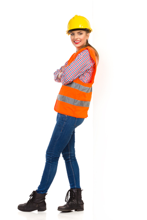 lumberjack shirt: Smiling young woman in orange reflective vest, lumberjack shirt, jeans and black boots, standing with arms crossed and leand on a white wall. Full length studio shot isolated on white. Stock Photo