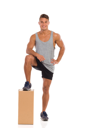 Smiling young man in black shorts and sneakers standing and holding one leg on carton box. Full length studio shot isolated on white.