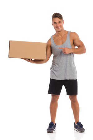 legs apart: Smiling young man in sorts clothes standing with legs apart, holding carton box in one hand and pointing. Full length studio shot isolated on white.