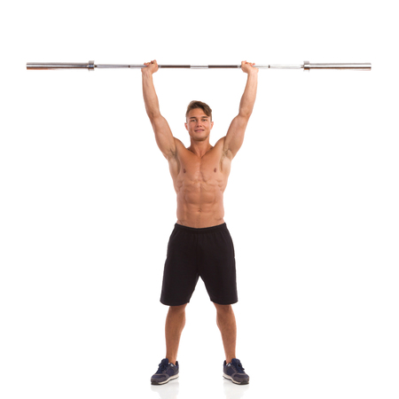 barbell: Muscular man holding a barbell over his head. Front view. Full length studio shot isolated on white. Stock Photo