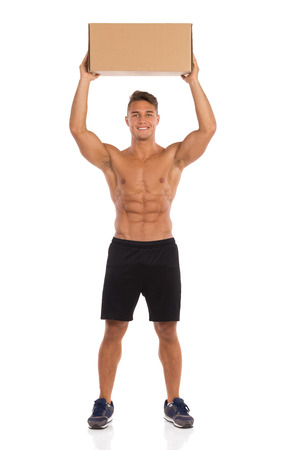 legs apart: Smiling fit young man in black shorts and sneakers standing with legs apart and holding carton box over his head. Full length studio shot isolated on white.