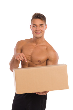 waist shot: Smiling young man in black shorts and sneakers standing with legs apart, holding carton box in one hand and pointing. Waist up studio shot isolated on white.