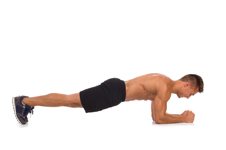 leaning on elbows: Muscular man does a isometric stomach exercise, side view. Full length studio shot isolated on white.
