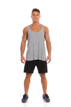 persona de pie: La sonrisa del hombre joven del ajuste en pantalones negros, camisa suelta y zapatillas de deporte de pie con las piernas separadas. Estudio de longitud completa aislado disparo en blanco.