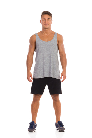 Smiling young fit man in black shorts, loose shirt and sneakers standing with legs apart. Full length studio shot isolated on white.