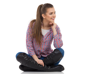 lumberjack shirt: Smiling young woman in lumberjack shirt, jeans and black boots sitting on a floor with legs crossed and looking away. Full length studio shot isolated on white. Stock Photo