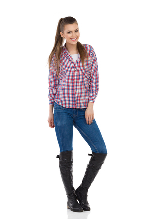 lumberjack shirt: Young woman standing in jeans, black boots and lumberjack shirt. Full length studio shot isolated on white. Stock Photo