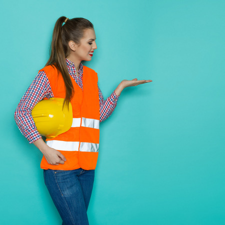 lumberjack shirt: Smiling young woman in orange reflective vest, lumberjack shirt and jeans holding yellow hardhat under the arm and posing with open hand and looking at it. Three quarter length studio shot on turquoise background.