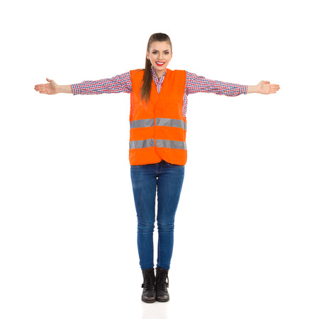 horizontally: Young woman in orange reflective vest, lumberjack shirt, jeans, black boots,standing with horizontally arms outstretched. Full length studio shot isolated on white. Stock Photo