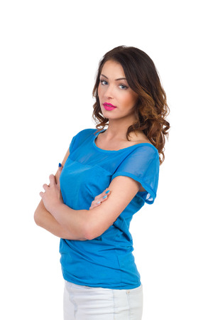 three quarter length: Young woman in blue top posing with arms crossed. Three quarter length studio shot isolated on white.