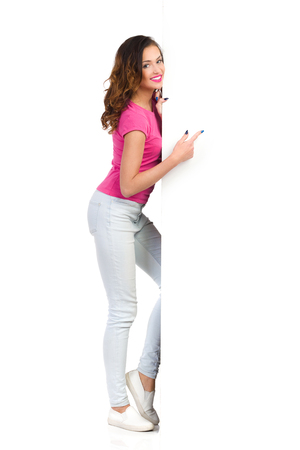 Smiling young woman standing behind big white banner and peeking. Full length studio shot isolated on white.