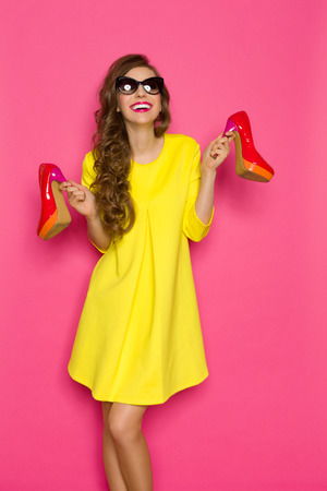 Smiling young woman in yellow mini dress and sunglasses holding two red high heels. Three quarter length studio on pink background.