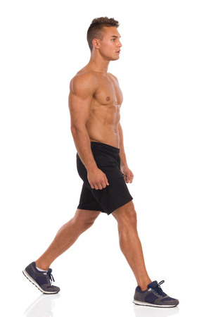 waiting posture: Muscular man standing with legs apart before split squat, side view. Full length studio shot isolated on white.