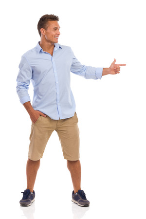 legs apart: Smiling young man in beige shorts, blue shirt and sneakers standing with legs apart, holding one hand in pocket and pointing with the other hand. Full length studio shot isolated on white. Stock Photo