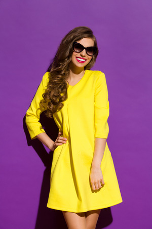 Beautiful smiling girl in sunglasses posing in yellow mini dress. Three quarter length studio shot on violet background. Standard-Bild