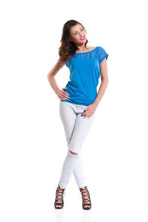 legs crossed at knee: Smiling young woman in blue top, jeans and high heels standing with legs crossed at knee, holding hand on hip and looking away. Full length studio shot Isolated on white.