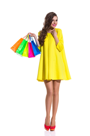 Smiling elegance young woman in red high heels and yellow mini dress standing and holding colorful shopping bags. Full length studio shot isolated on white.