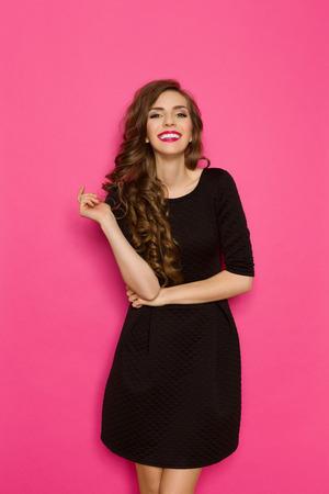 Smiling elegance woman in classic black mini dress. Three quarter length studio shot on pink background. Stockfoto
