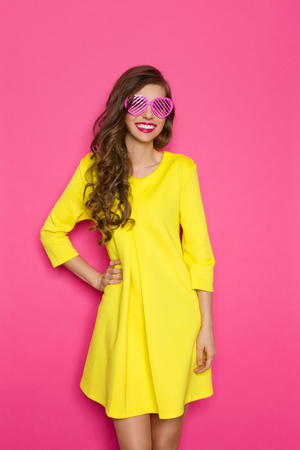 three quarter length: Smiling beautiful girl in pink sunglasses and yellow mini dress posing with hand on hip. Three quarter length studio shot on pink background.