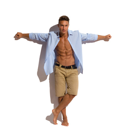 ankles sexy: Handsome young man in unbuttoned blue shirt and beige shorts standing barefoot against sunny wall and holding arms outstretched. Full length studio shot isolated on white.