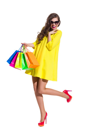 Laughing young woman in yellow mini dress and red high heels standing on one leg and holding colorful shopping bags. Full length studio shot isolated on white.