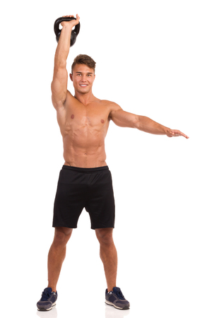 human hands: Smiling muscular man in sport shorts and sneakers posing and holding a kettlebell in raised hand. Full length studio shot isolated on white.