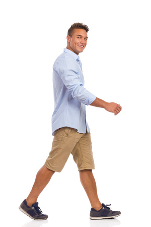 ベージュのショート パンツ、青いシャツ、スニーカー ウォーキングで笑顔の若い男。完全な長さのスタジオ撮影に分離白。