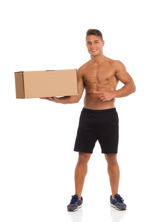 apart: Smiling young man in black shorts and sneakers standing with legs apart, holding carton box in one hand and pointing. Full length studio shot isolated on white.