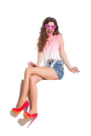 legs crossed at knee: Shouting sexy woman in pink heart shaped sunglasses, pink top, jeans shorts and red high heels sitting at the top of white banner. Full length studio shot isolated on white.