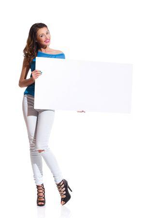 modelos posando: Mujer joven sonriente en pantalones vaqueros rasgados y una camisa rosa de pie y sosteniendo el cartel blanco. tiro del estudio de longitud completa aislado en blanco Foto de archivo