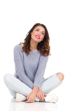 Mujer joven sonriente en suéter y pantalones vaqueros, sentado en el suelo con las piernas cruzadas mirando hacia arriba. Estudio de longitud completa aislado disparo en blanco.