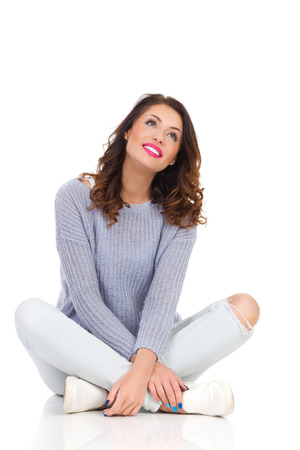 Smiling young woman in sweater and jeans sitting on a floor with legs crossed looking up. Full length studio shot isolated on white.