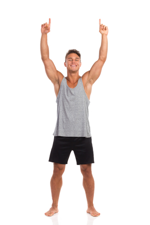 legs apart: Smiling muscular man standing barefoot with both arms raised and pointing up. Full length studio shot isolated on white.